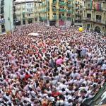 Se puede ver la plaza del ayuntamiento de Pamplona en pleno 6 de julio llena de personas. Dos tercios de la imagen los ocupan pequeñas cabezas tintadas de blanco y rojo. Imagen multitudinaria