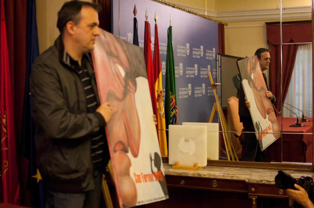 Se puede puede ver a Javier Erice con el cartel en la mano y su reflejo en el espejo de la sala de prensa del ayuntamiento de Pamplona