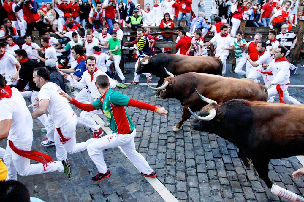 Tres corredores delante de los toros del encierro en el tramo de Telefónica.