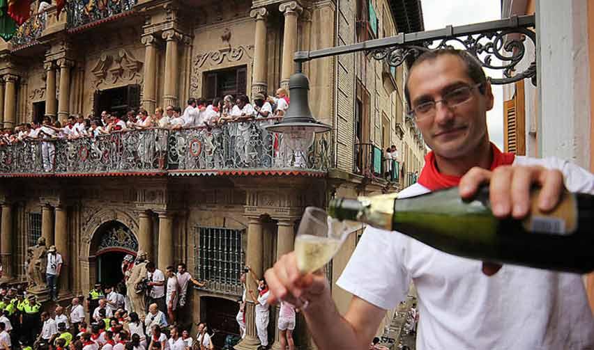 Se puede ver a Mikel Ollo preparándose una copa de champán en un balcón donde se adivina que está muy cerca del balcón donde se lanza el chupinazo de San Fermin