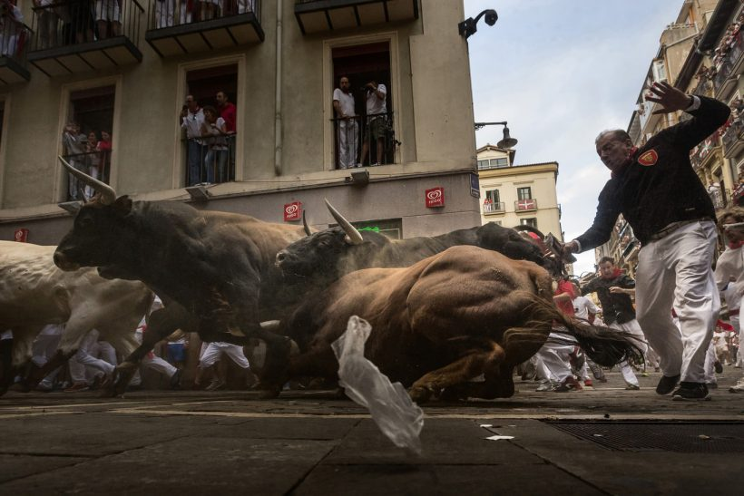 Revelers run chased by 'El Tajo y La Reina' ranch fighting bulls as they turn Estafeta corner during a running of the bulls of the San Fermin festival in Pamplona, Spain, Wednesday, July 8, 2015. Revelers from around the world arrive in Pamplona every year to take part on some of the eight days of the running of the bulls.