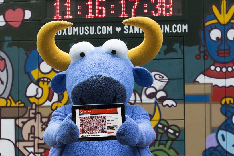 Mister Testis, el toro azul de Kukuxumusu, muestra la nueva web Sanfermin.com en su tablet.
