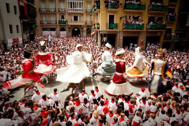 Imágenes de los gigantes bailando con las faldas al aire en plena plaza del Ayuntamiento de Pamplona por Sanfermin. Una foto llena de colorido y movimiento.