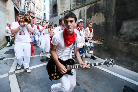 Imagen de un guitarrista tocando por la calle Jarauta mientras saca la lengua. PErtenece a una electrocharanga que va detrás y la guitarra es eléctrica