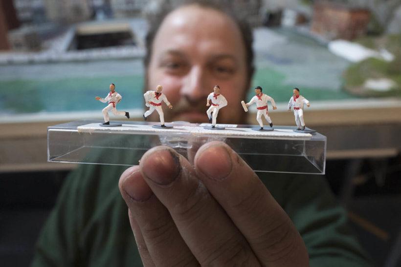 Un hombre enseña cinco corredores en miniatura del encierro de Sanfermin para la exposición.