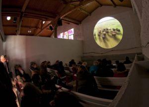 Imagen de la visita en las cuadras de caballos de la plaza de toros donde se puede ver un audiovisual de la vida del toro.