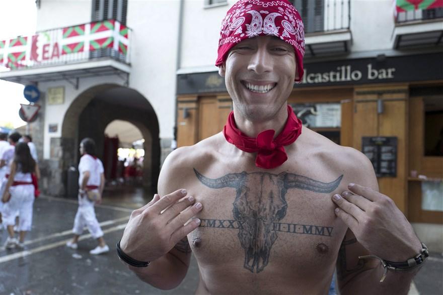 Un chico enseña tu tatuaje de un toro que le ocupa todo el pecho, que lleva desnudo.