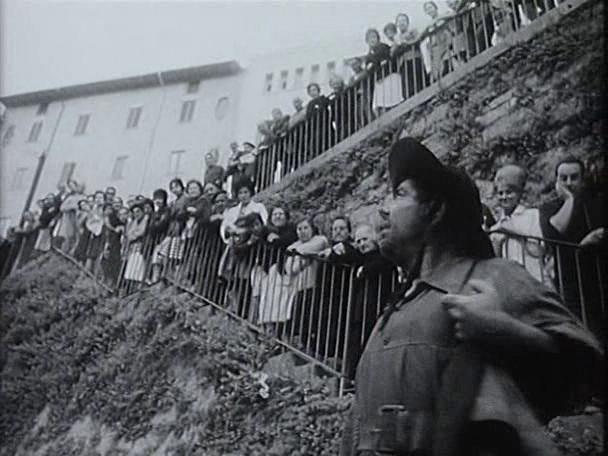 Se ve al actor que interpreta a Sancho Panza ataviado con ropa de campo y sombrero en primer plano, con unas doscientas personas dispuestas en la cuesta de Santo Domingo para ver el encierro