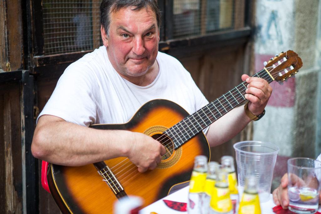 Señor tocando la guitarra de risas en Sanfermin