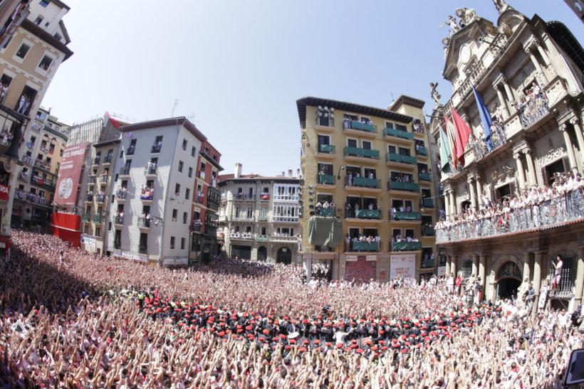 Imagen del chupinazo de san fermin lleno de gente y con los gaiteros saliendo del ayuntamiento