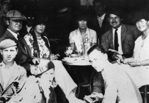 Ernest Hemingway acompañado de amigos tomando unas copas en la plaza del castillo de Pamplona en 1925