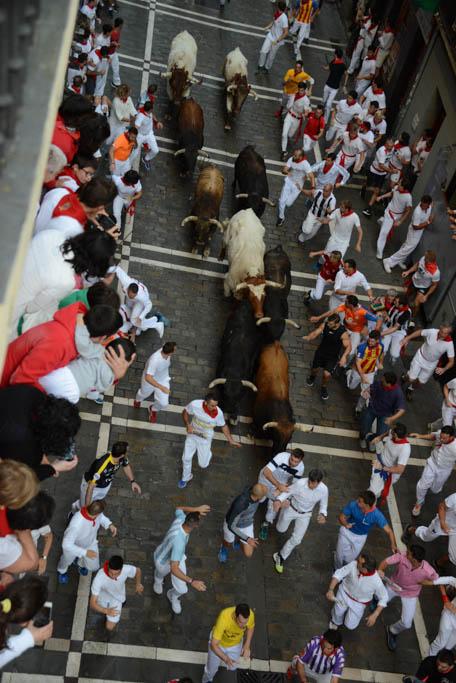 Los seis toros de la palmosilla por la calle estafeta de pamplona en un plano desde un balcón donde se aprecia a todos los animles abriéndose paso