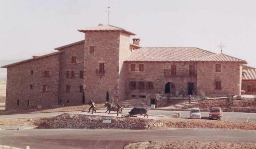 Imagen general del Hostal del Toro de 1970. Se puede ver el monumento al encierro en primer plano junto a dos coches aparcados.