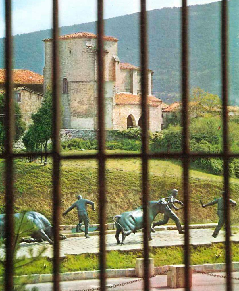Preciosa imagen del monumento al encierro con una iglesia de fondo, filtrando la imagen por los barrotes de una de las ventanas del Hostal del Toro. La imagen es de 1969
