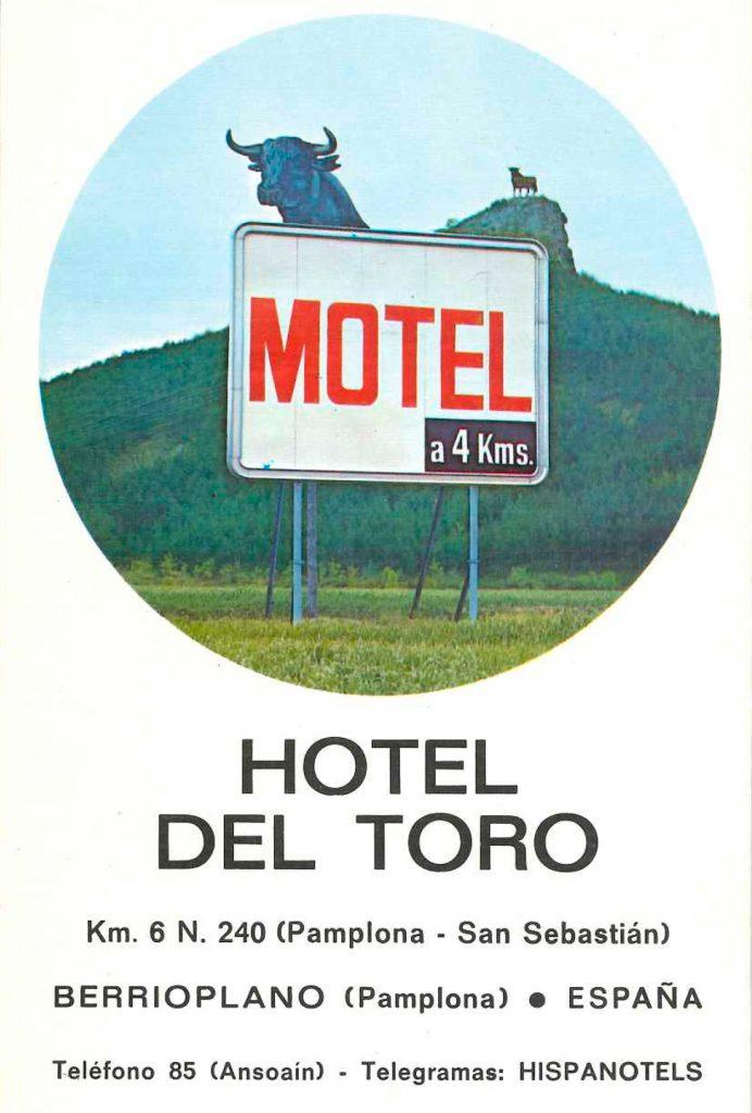 En primer plano un cartel de carretera con la inscripción MOTEL, una silueta de todo en la parte superior y, de fondo, un monte con el toro de Osborne silueteando el horizonte.